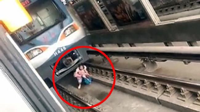 電車の前で蹲る自殺志願者
