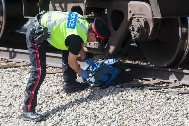 電車への飛び込み自殺者の遺品を調べる警官