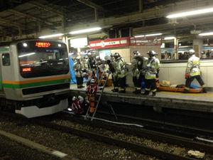 飛び込み自殺者の死体を駅のレールから搬出する様子